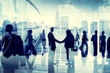 Imagem estilizada de várias pessoas caminhando. Entre elas, duas pessoas se cumprimentam. Ao fundo, como se vistas através de uma janela, silhuetas de edifícios